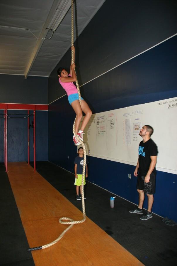 Tony teaching his kids how to climb the rope